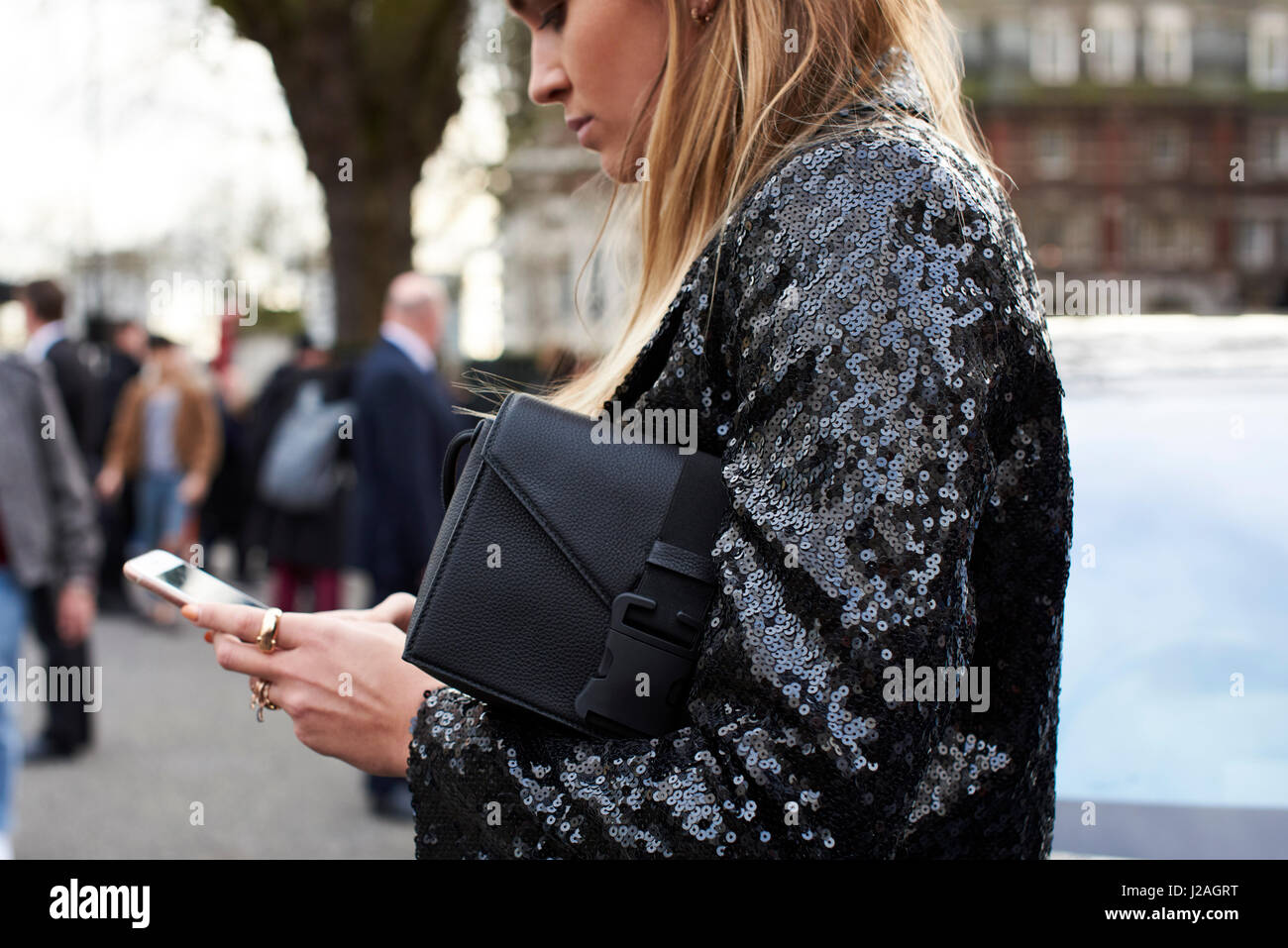 LONDON - FEBRUARY, 2017: Waist up view of woman using smartphone in street outside Christopher Kane fashion show, - Stock Image