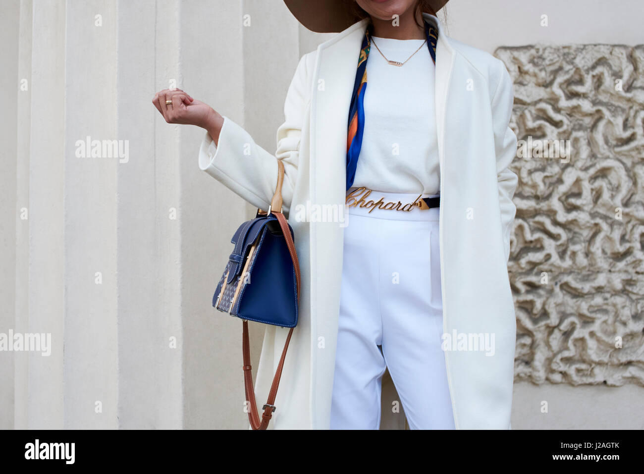 LONDON - FEBRUARY, 2017: Mid section of woman wearing white trousers, coat and metal Chopard belt holding a blue - Stock Image