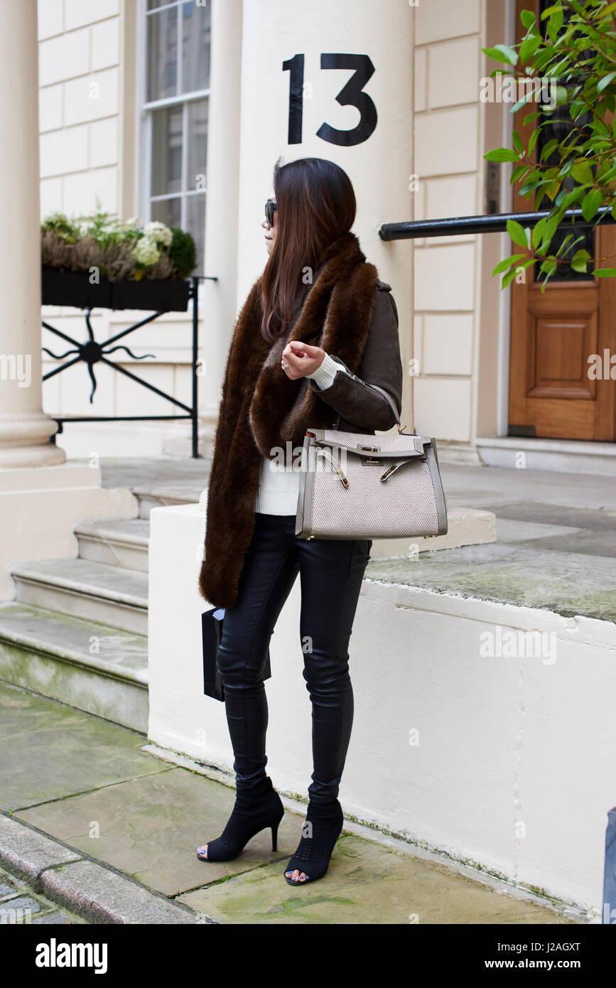 LONDON - FEBRUARY, 2017: Full length view of woman in open toe high heel ankle boots standing in the street holding - Stock Image