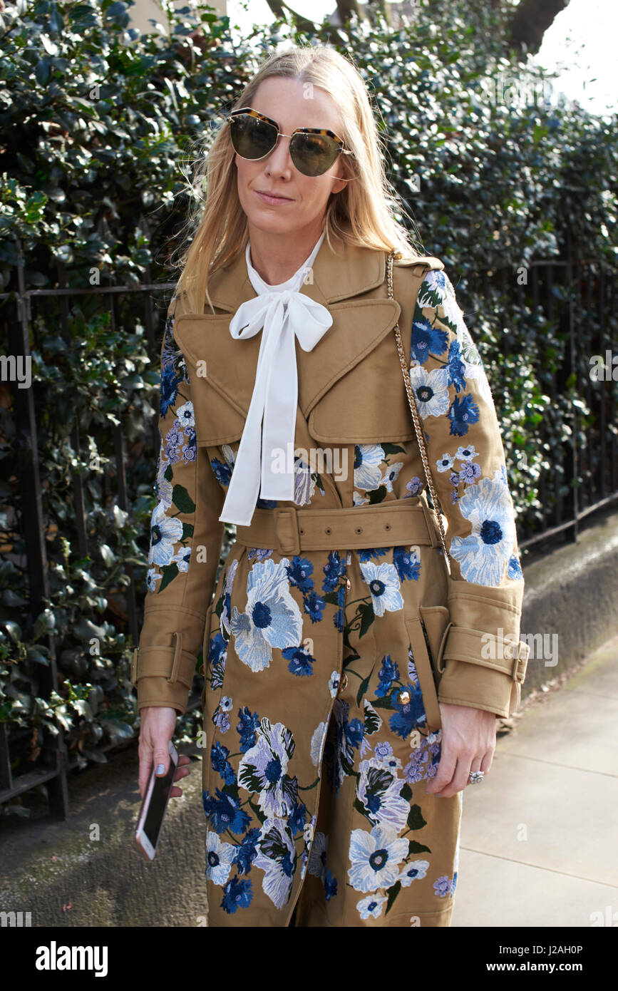 LONDON - FEBRUARY, 2017: Three quarter length view of woman wearing Erdem embroidered trench coat, bow collar, sunglasses, - Stock Image