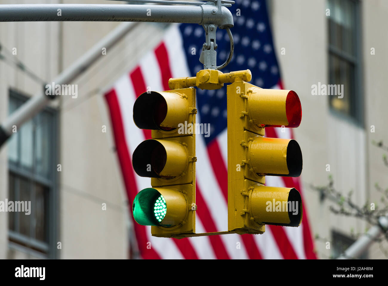 Green Traffic Light In Front Of American Flag, Immigration, Travel and Net Neutrality Restriction Concept - Stock Image