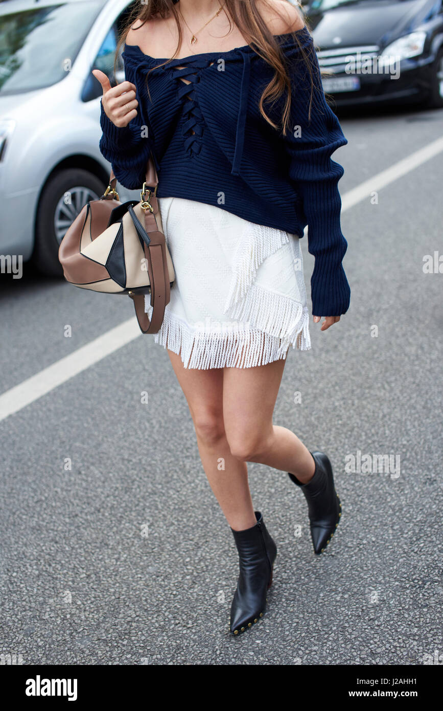 Woman in off shoulder top and fringed skirt walking, crop - Stock Image