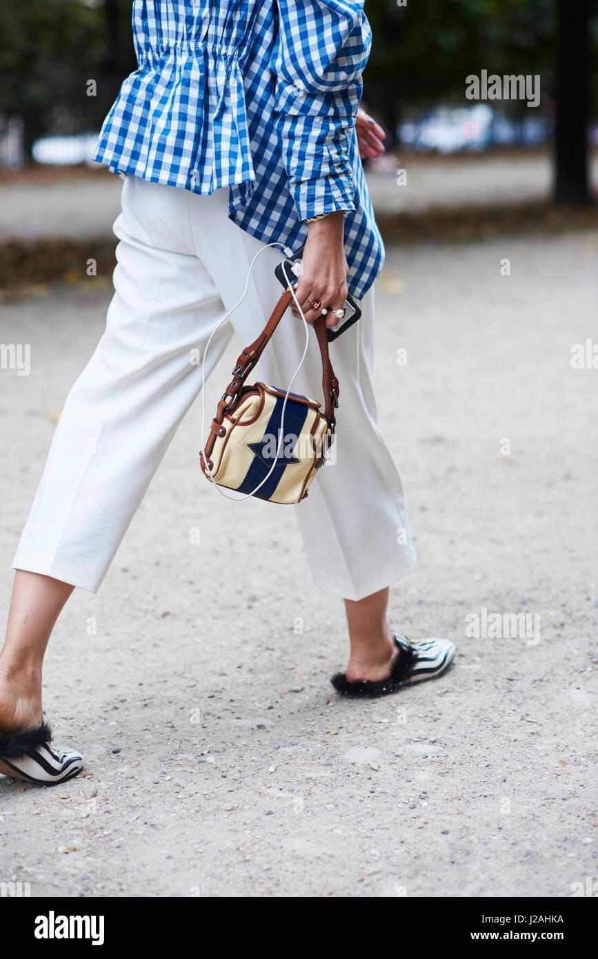 Woman walking wearing a gingham blouse, side view detail - Stock Image