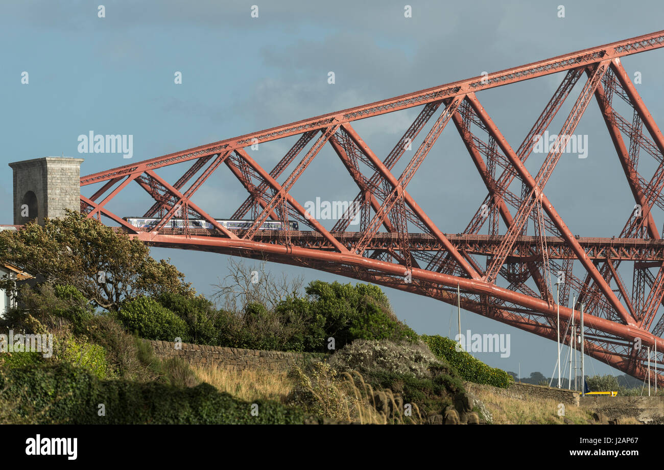 Train enters north end of Forth bridge, Scotland, United Kingdom - Stock Image