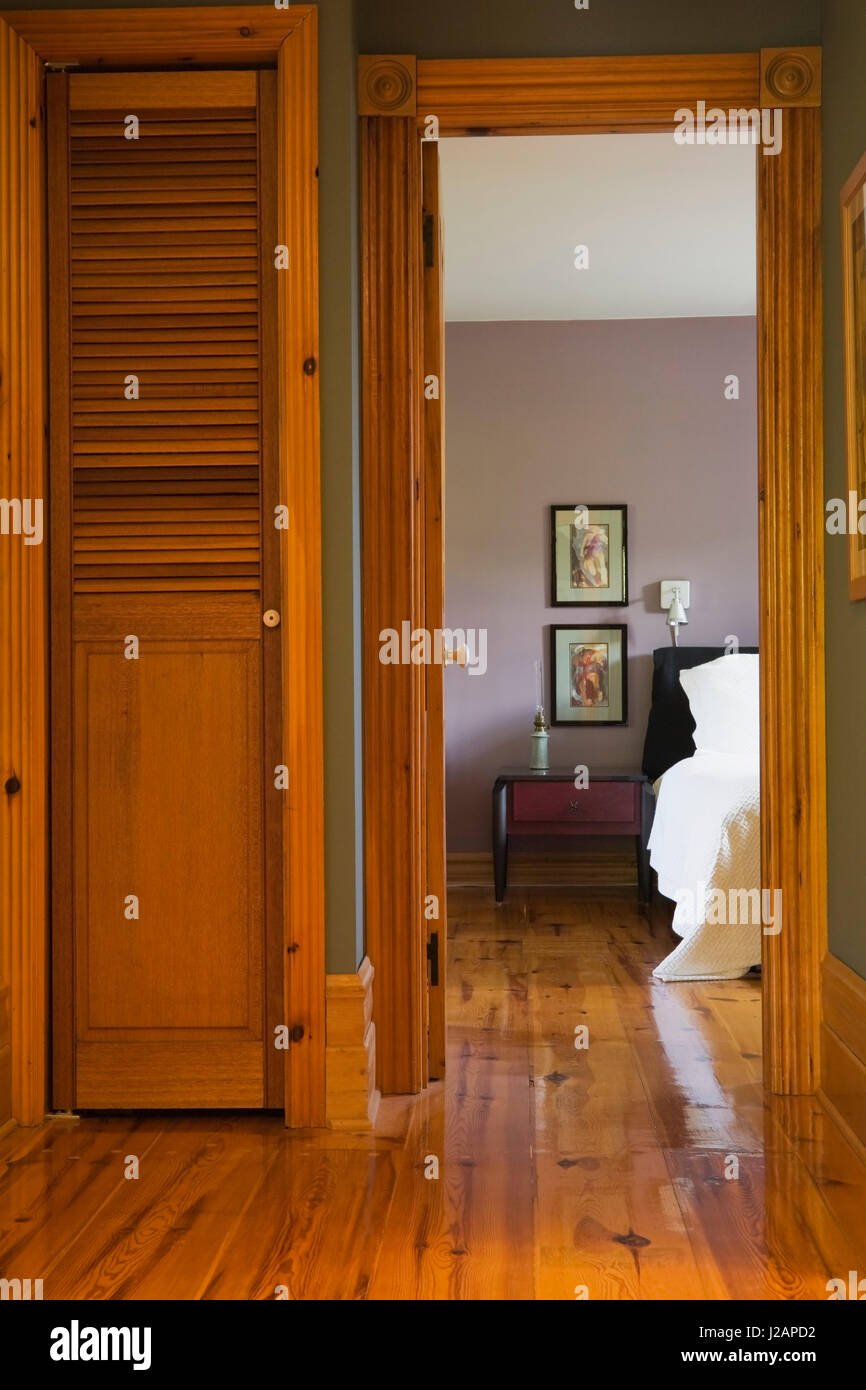 Hallway leading to the master bedroom on the upstairs floor inside a stacked log home - Stock Image