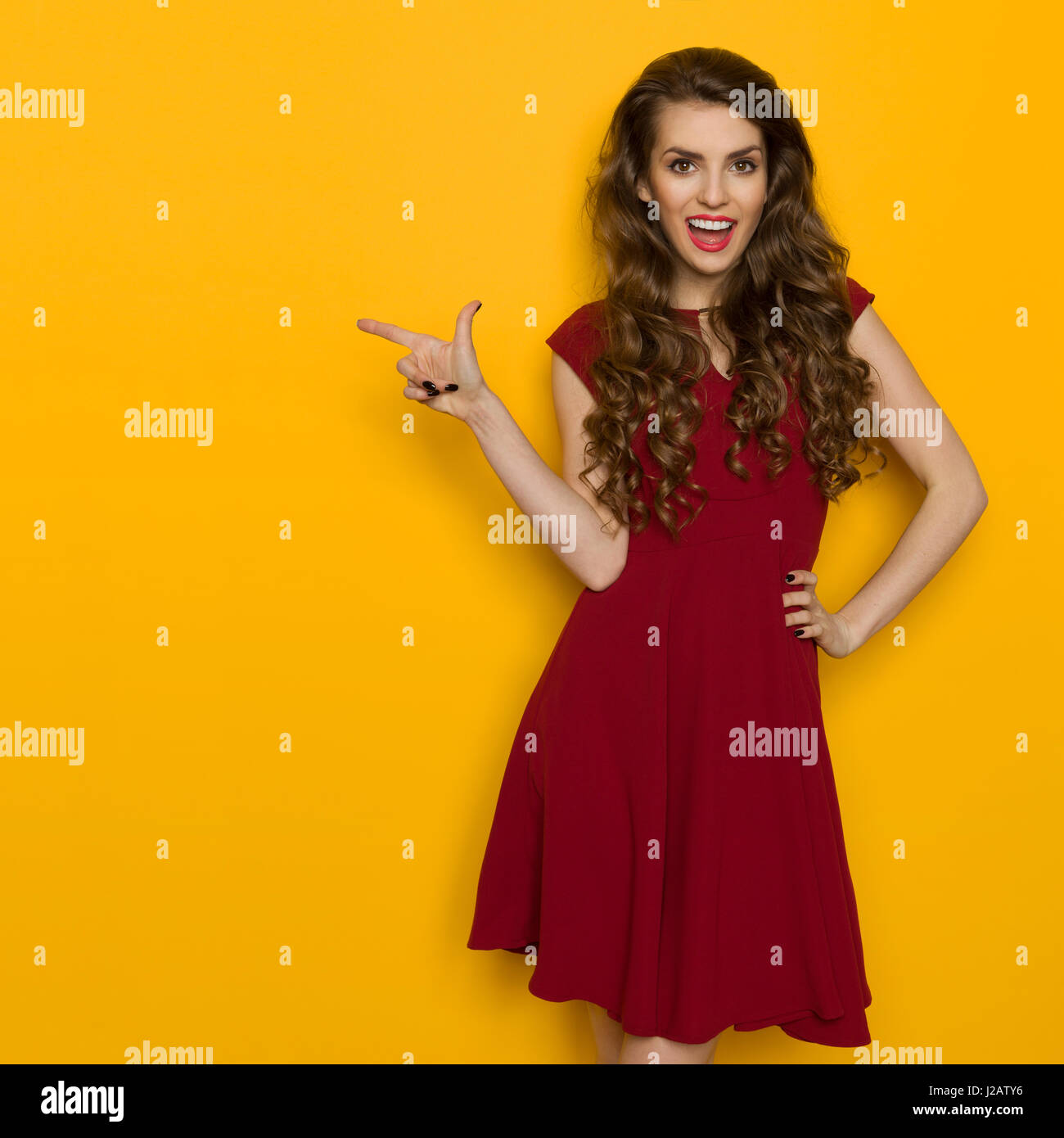 0ffe89209ac3 Beautiful young woman in maroon dress is pointing at copy space