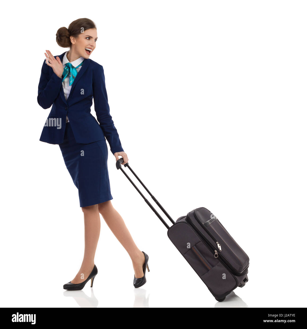 Smiling woman in blue suit and skirt is walking with trolley bag, looking back over shoulder and waving. Side view. - Stock Image