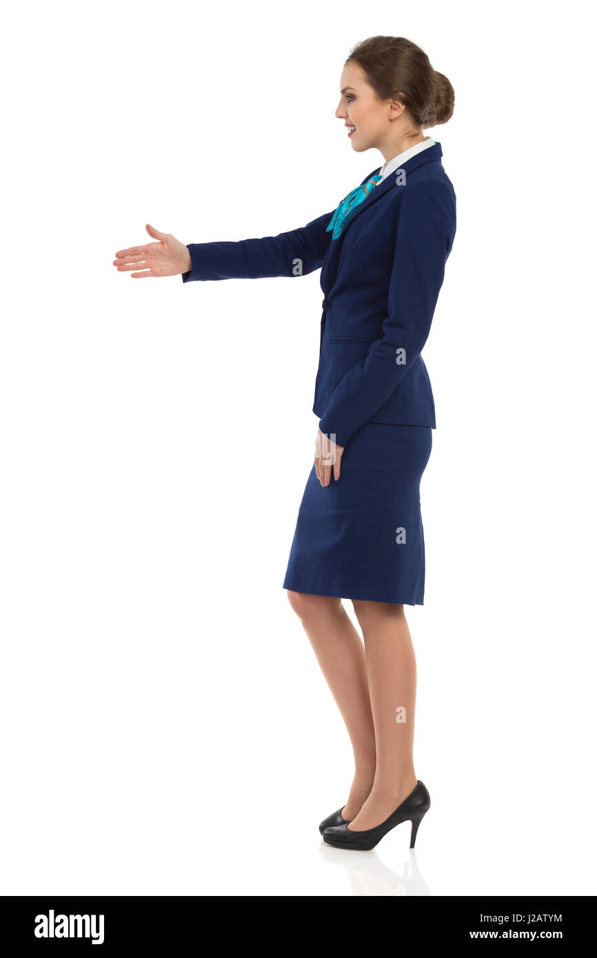 Young woman in blue formalwear and high heels is standing and giving hand for a handshake. Side view. Full length - Stock Image