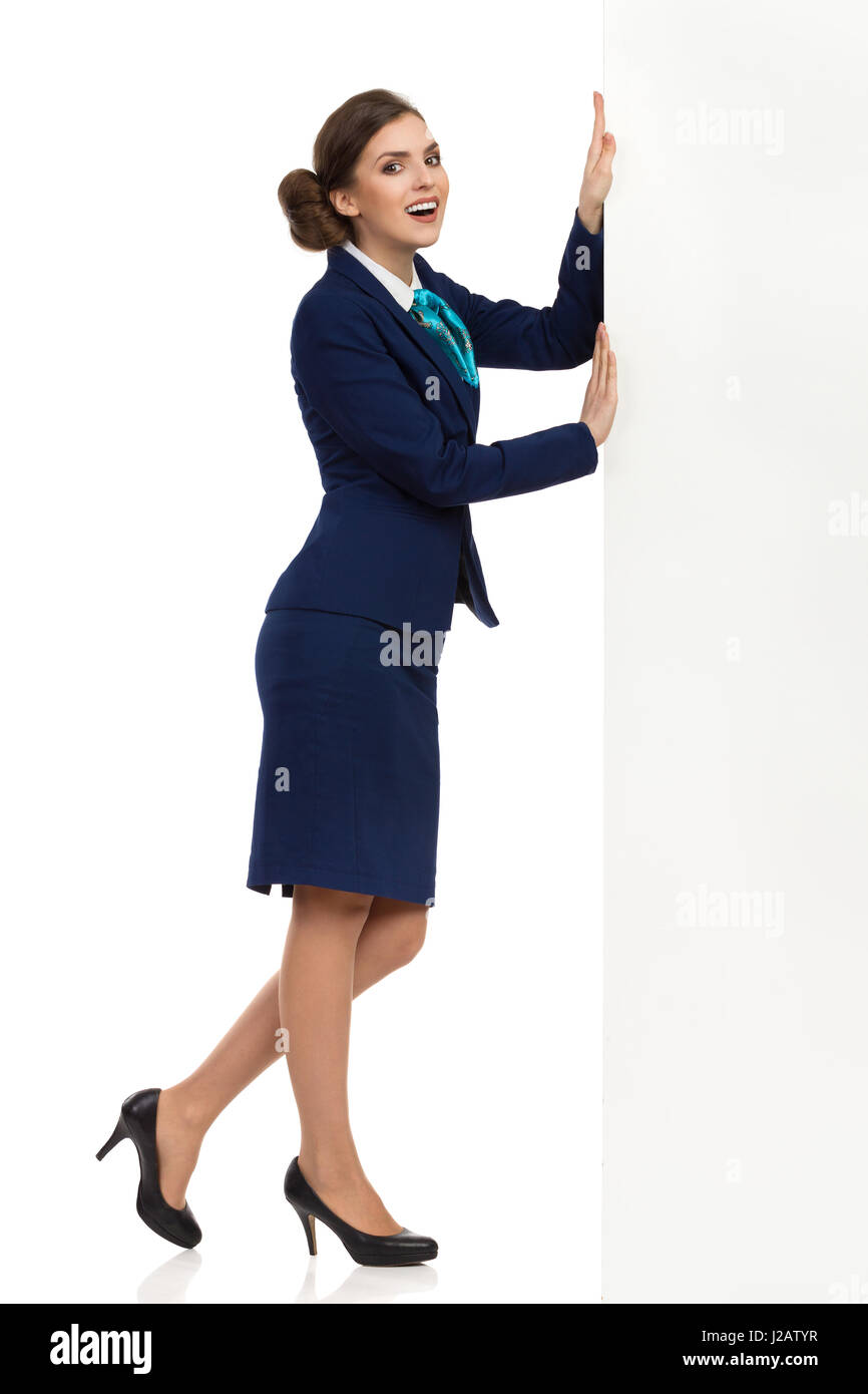Young woman in blue formalwear and high heels is pushing white banner and looking at camera. Side view. Full length - Stock Image
