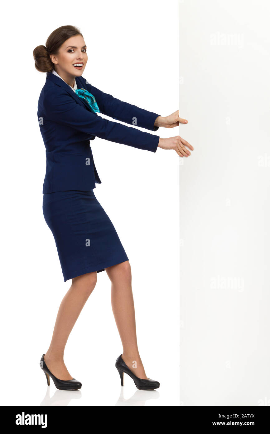 Young woman in blue formalwear and high heels is pulling white banner and looking at camera. Side view. Full length - Stock Image