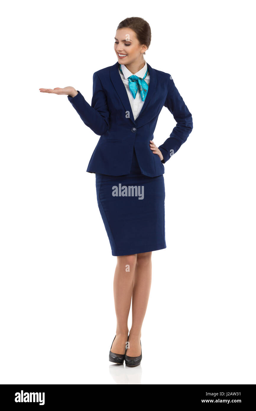 Smiling young businesswoman in blue formalwear and high heels is standing with hand raised and looking away. Front - Stock Image