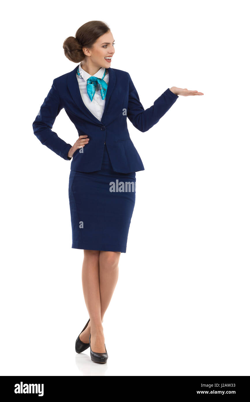 Young woman in blue formalwear and high heels is standing with hand raised, looking away and talking. Front view. - Stock Image