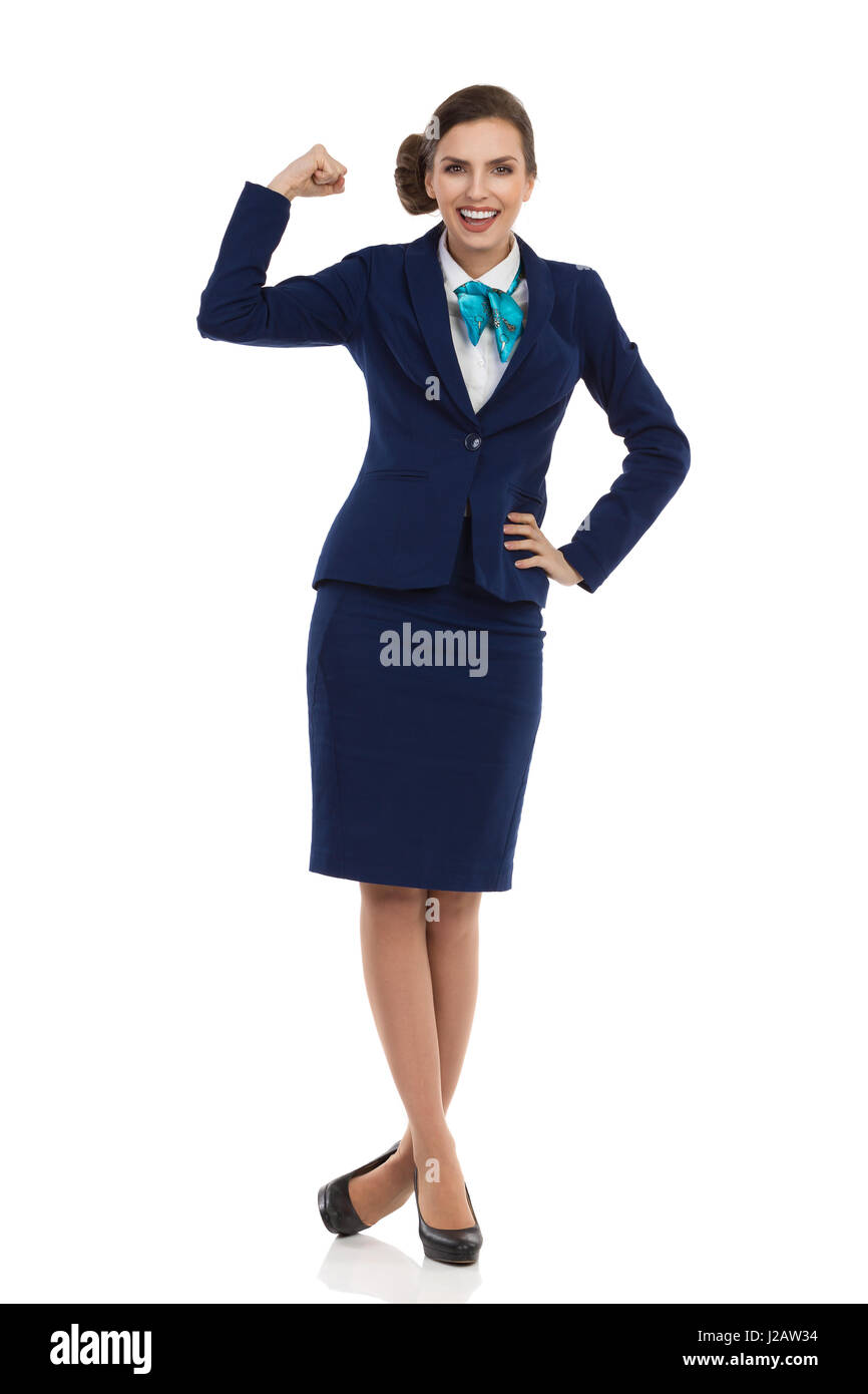 Young woman in blue formalwear and high heels is standing, smiling and flexing muscles. Front view. Full length - Stock Image