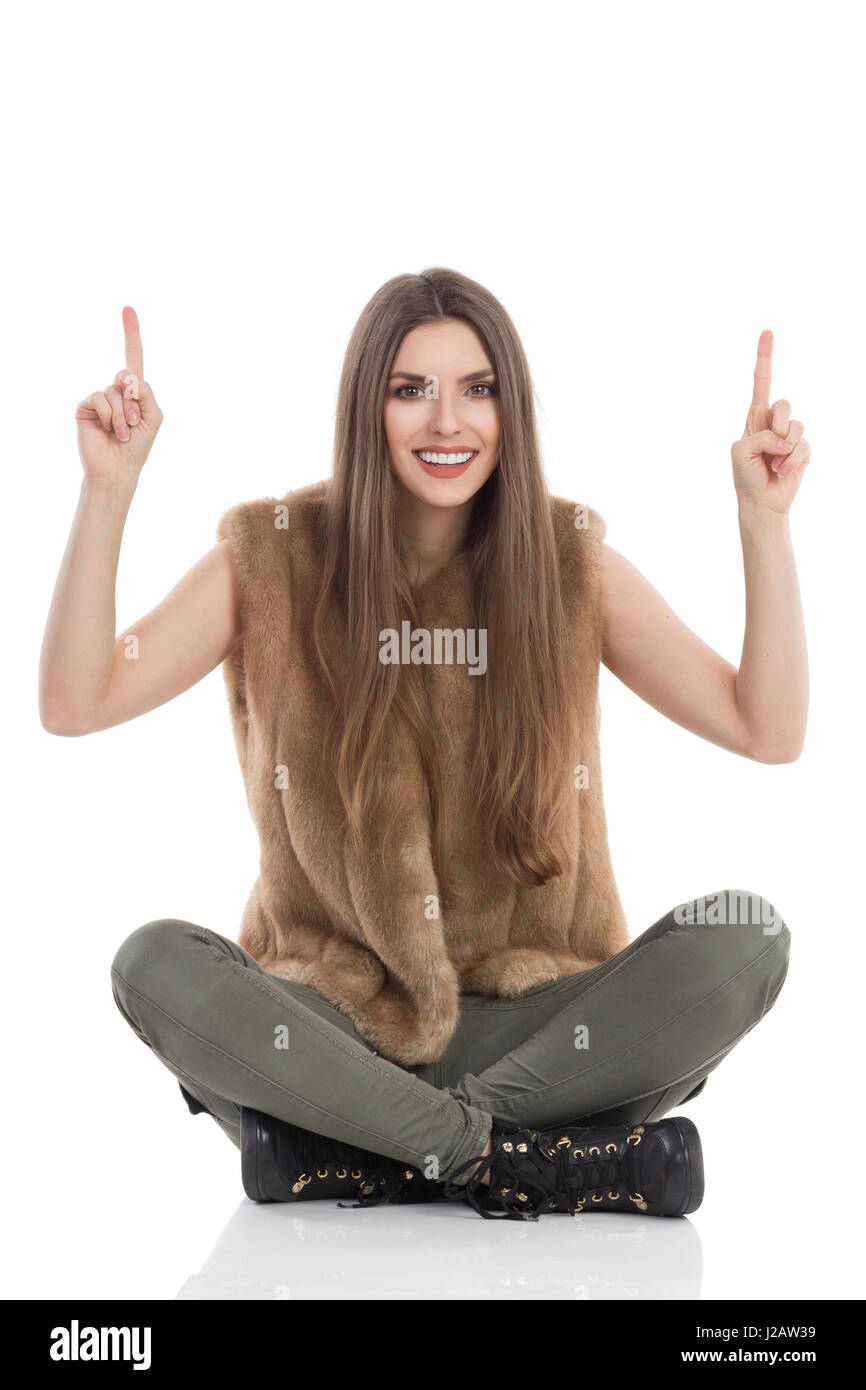 Beautiful young woman in brown fur waistcoat and khaki pants is sitting on floor legs crossed, holding arms raised - Stock Image