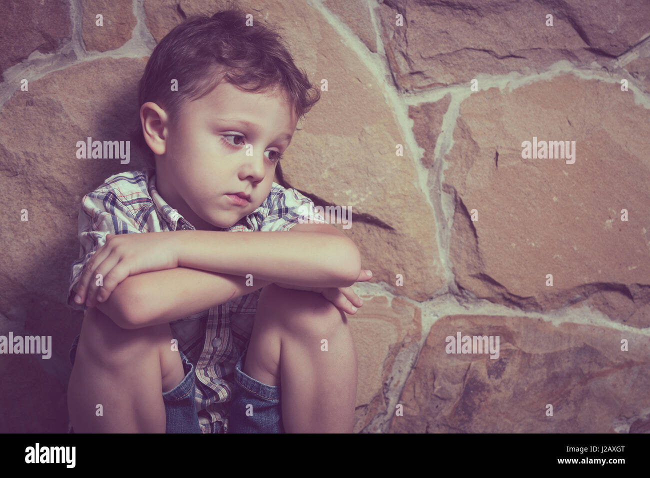 sad little boy sitting near the wall at the day time - Stock Image