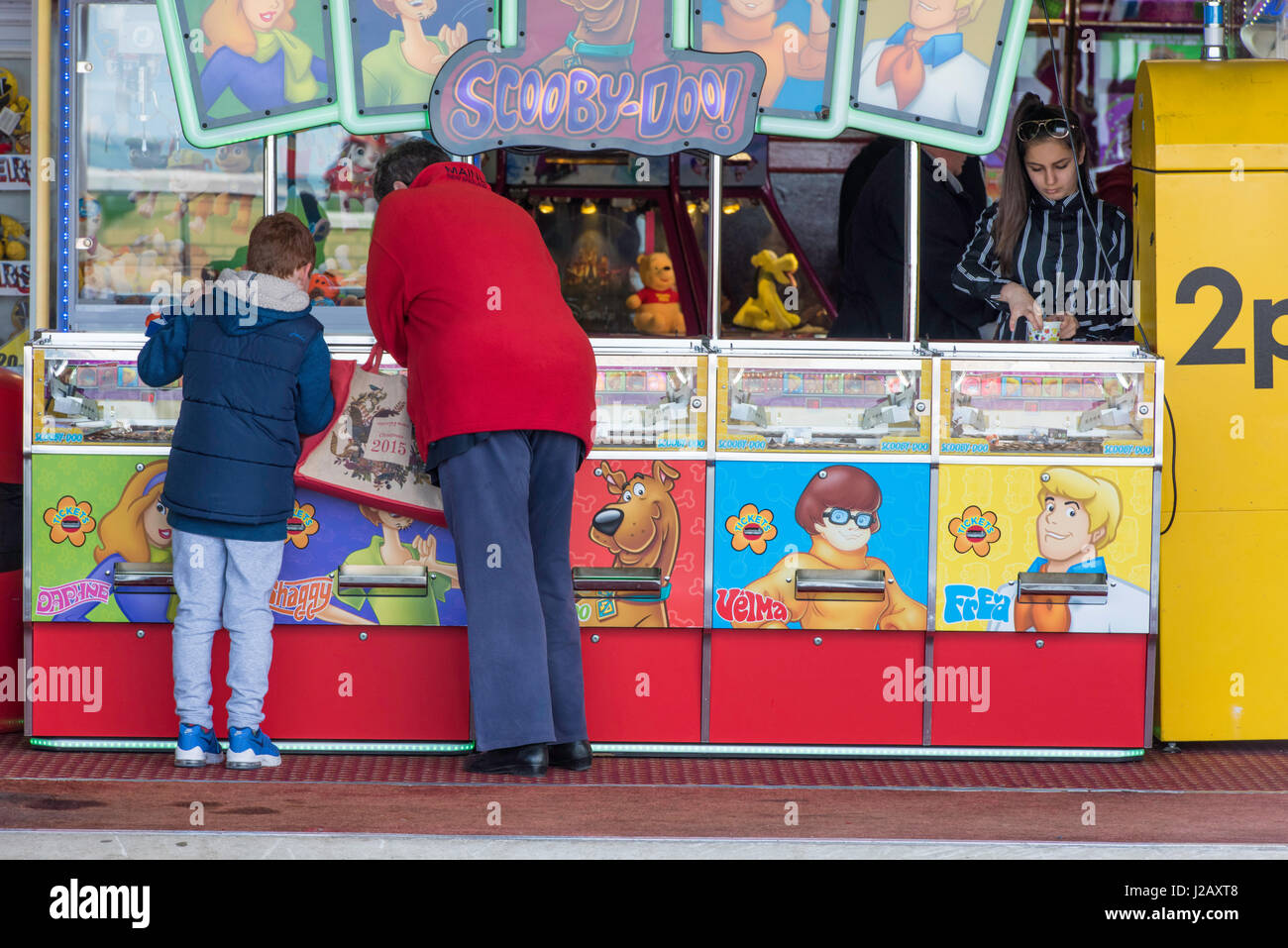 People paying an a two pence'Scooby-do' slot machine in an amusement arcade. - Stock Image