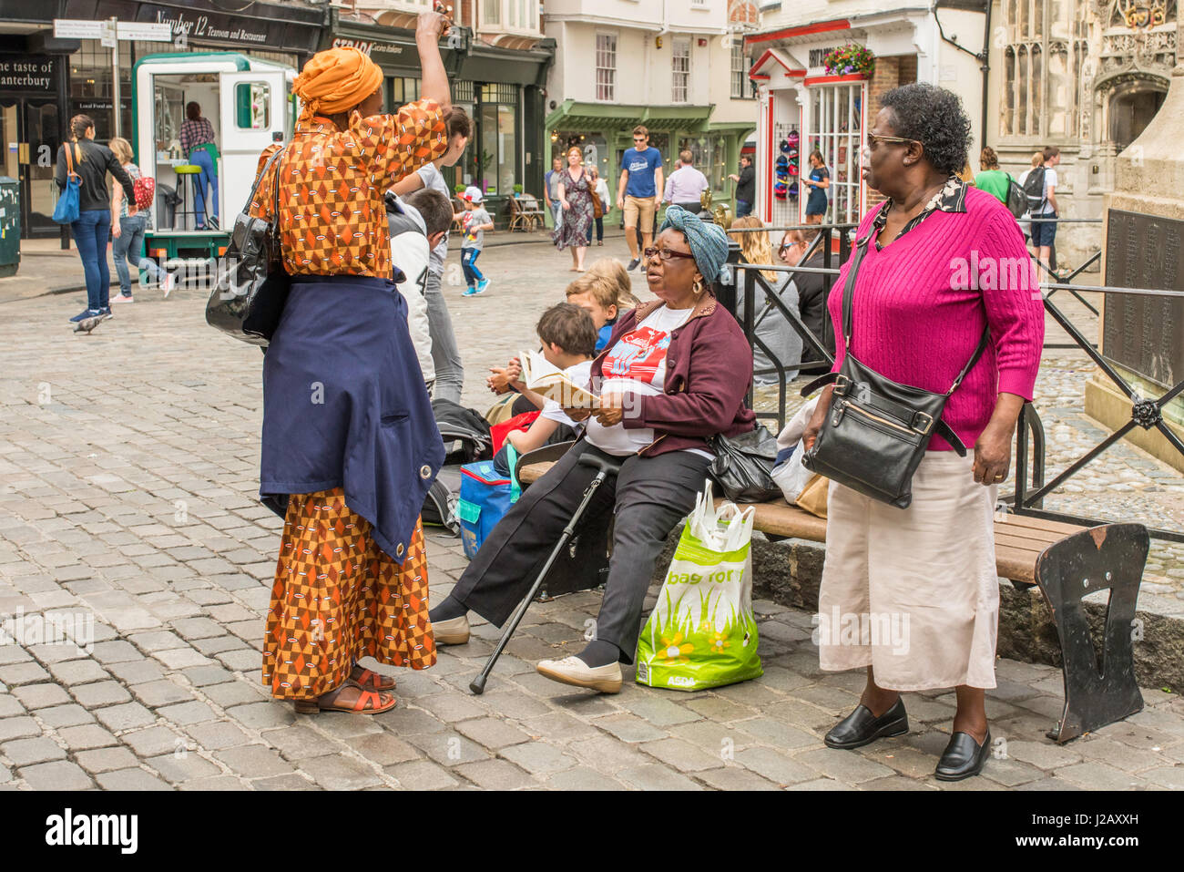 A group of female friends who have travelled from London to Canterbury for a day out taking some time to rest before - Stock Image