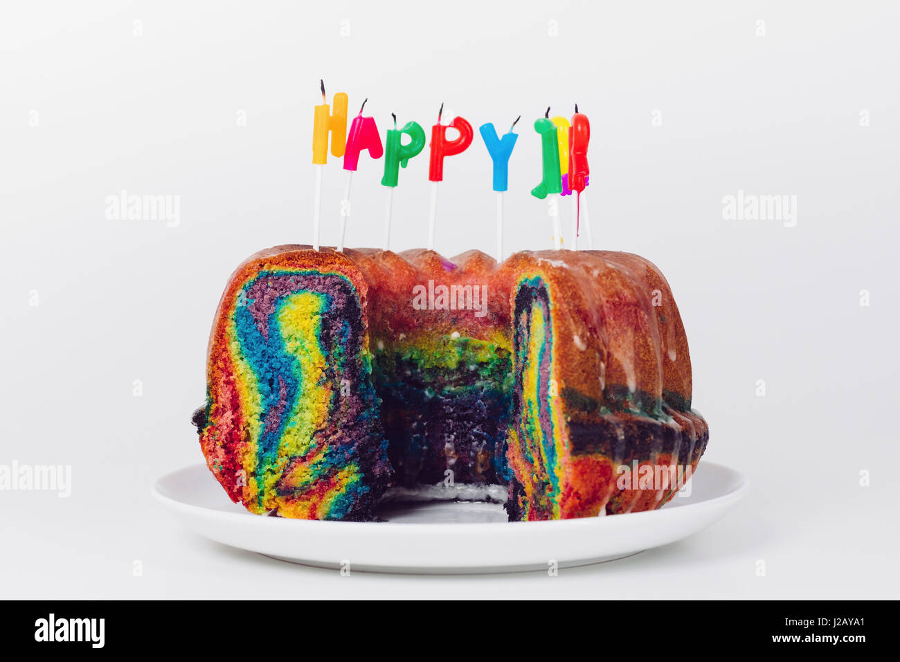 Close Up Of Birthday Candles On Rainbow Cake In Plate Against White Background