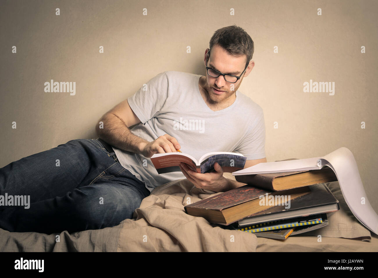 Young man studying on bed - Stock Image