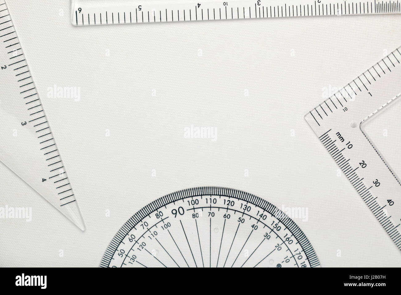 Geometry instruments creating copy space against white background - Stock Image