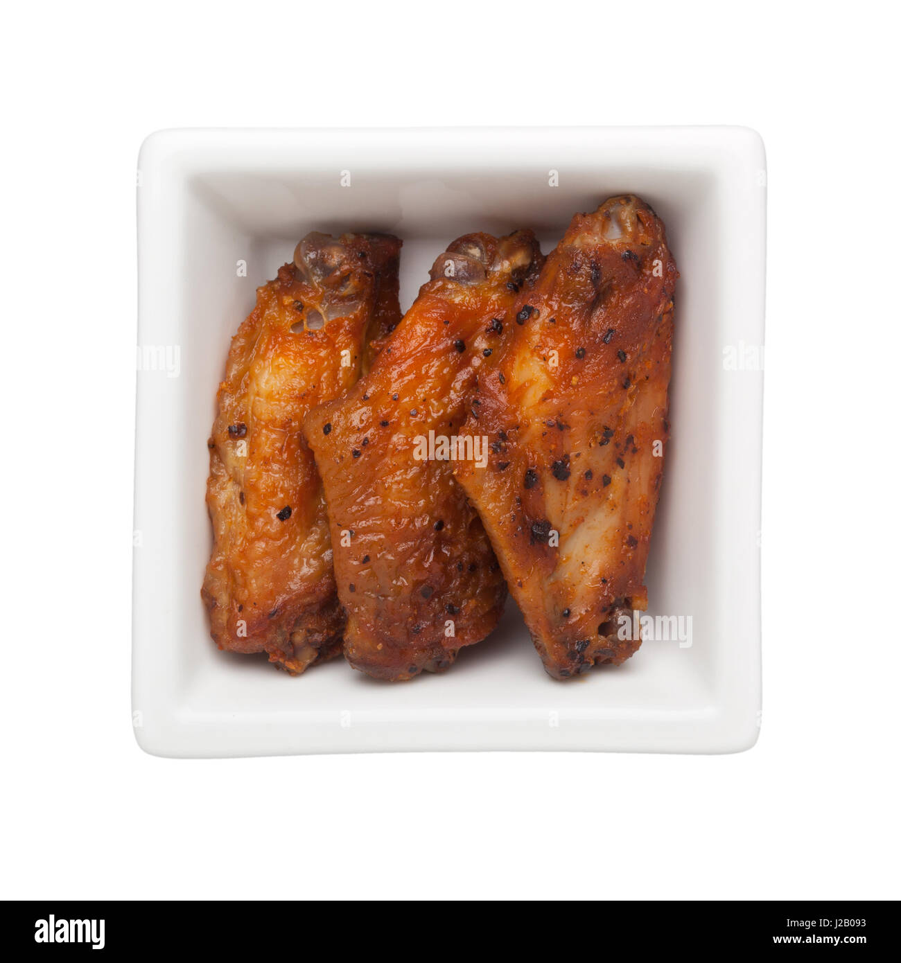 Fried chicken winglets in a square bowl isolated on white background - Stock Image