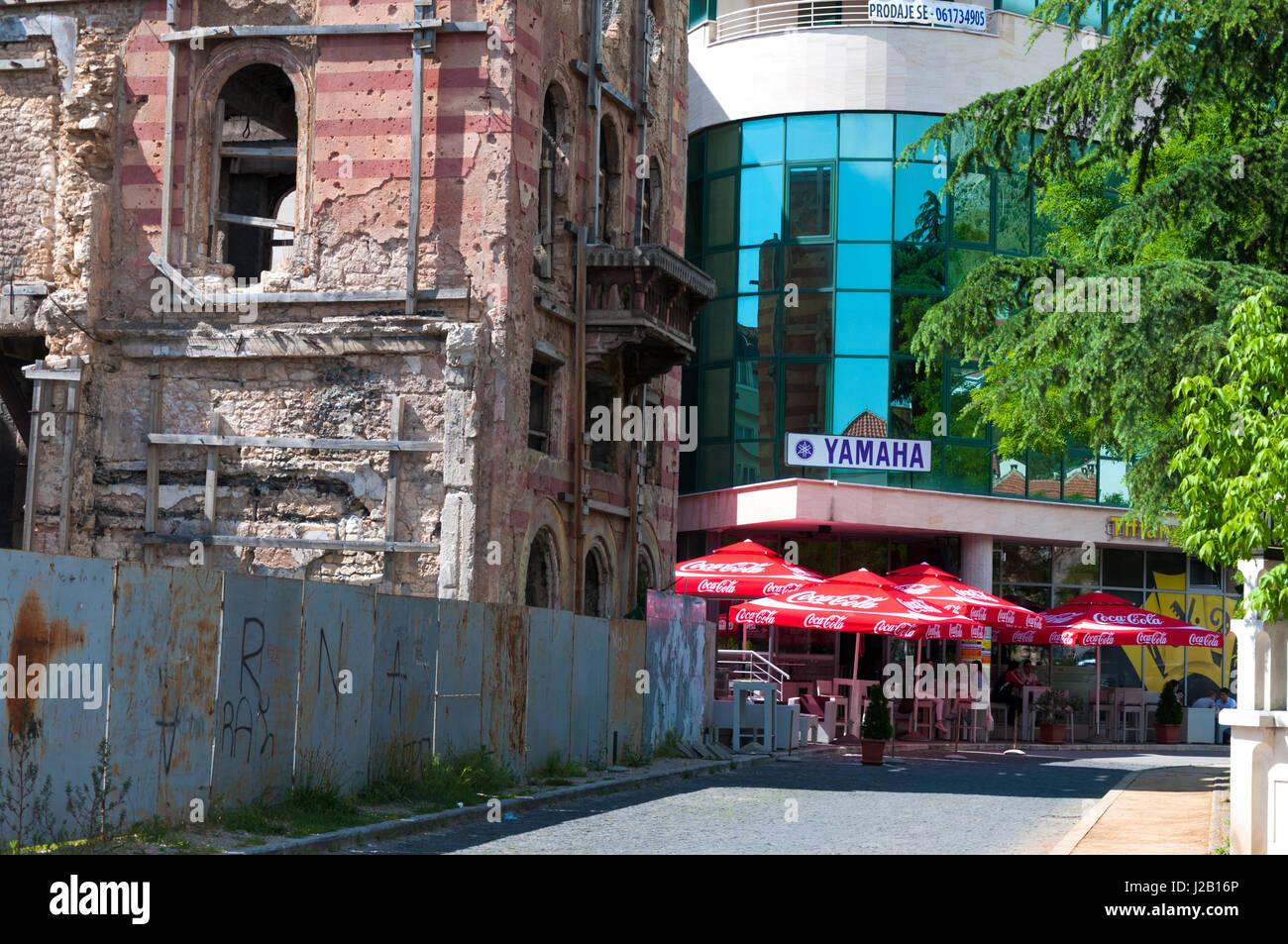 Mostar,  Bosnia and Herzegovina, War damaged building and modern new block. Rebuilding after war. - Stock Image