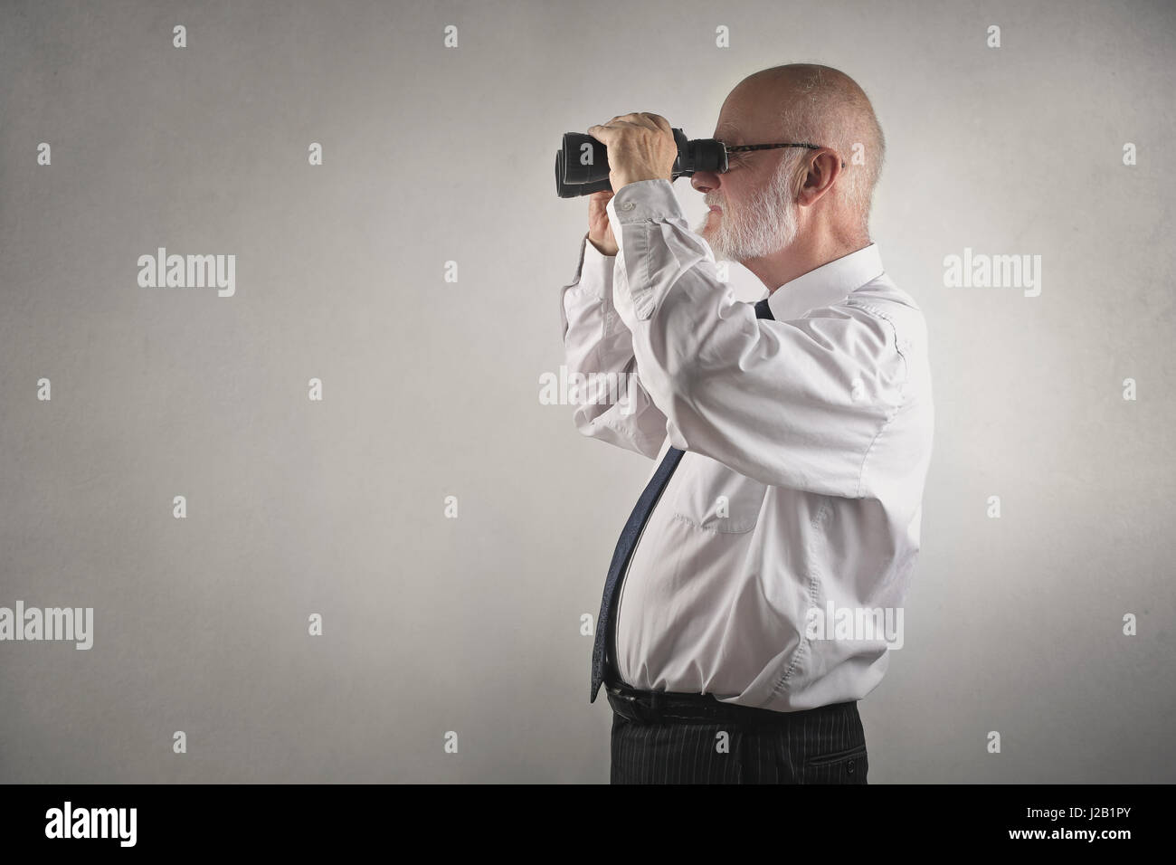 Old businessman looking with telescope - Stock Image