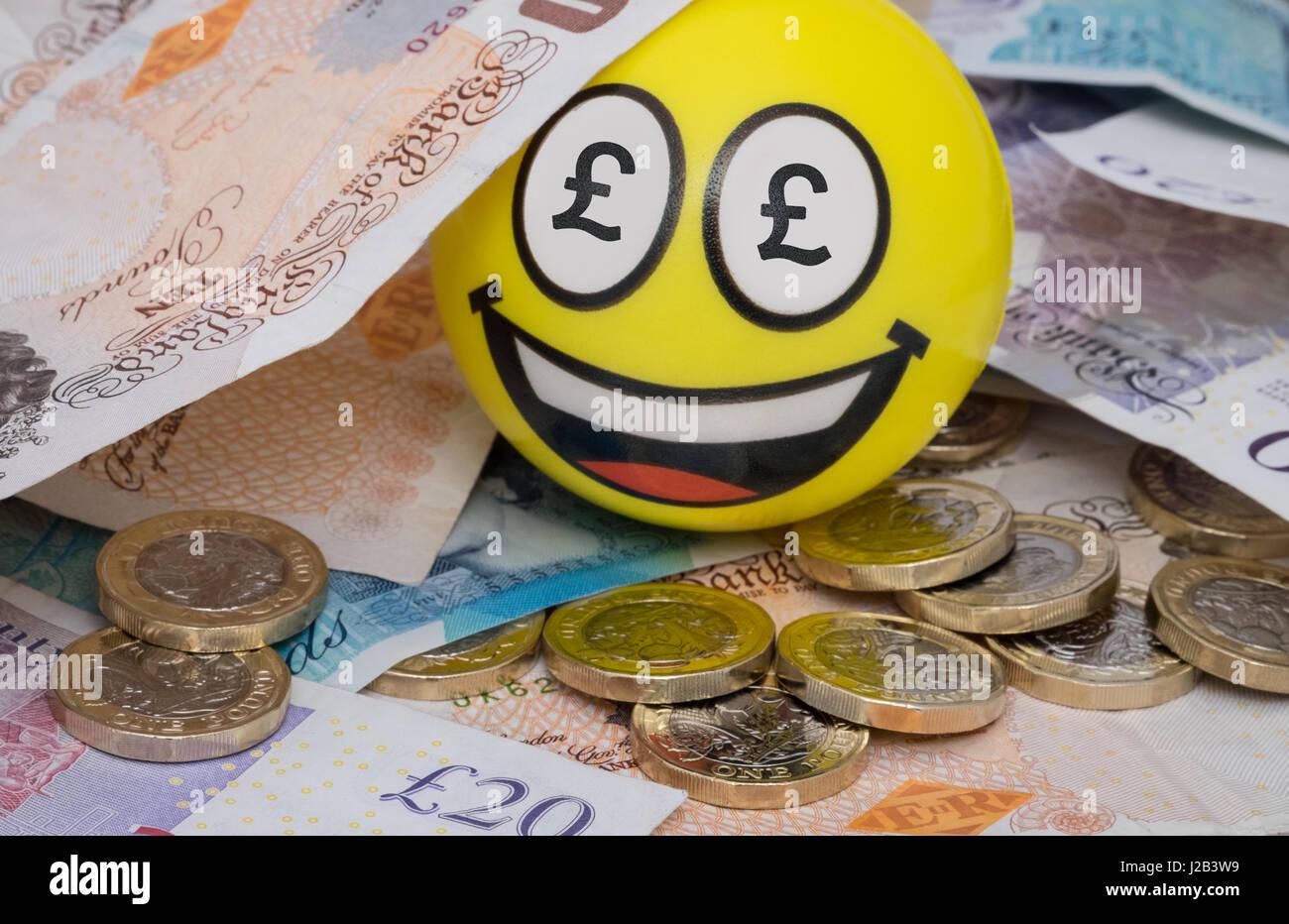 Smiling emoji face in uk money - Stock Image