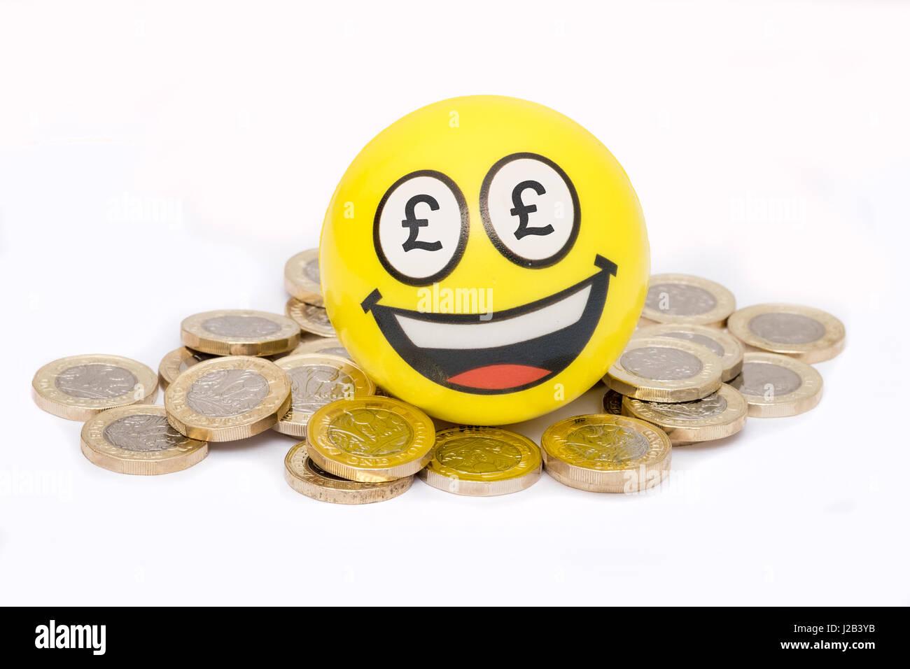 Happpy emoji on pile of british pound coins - Stock Image