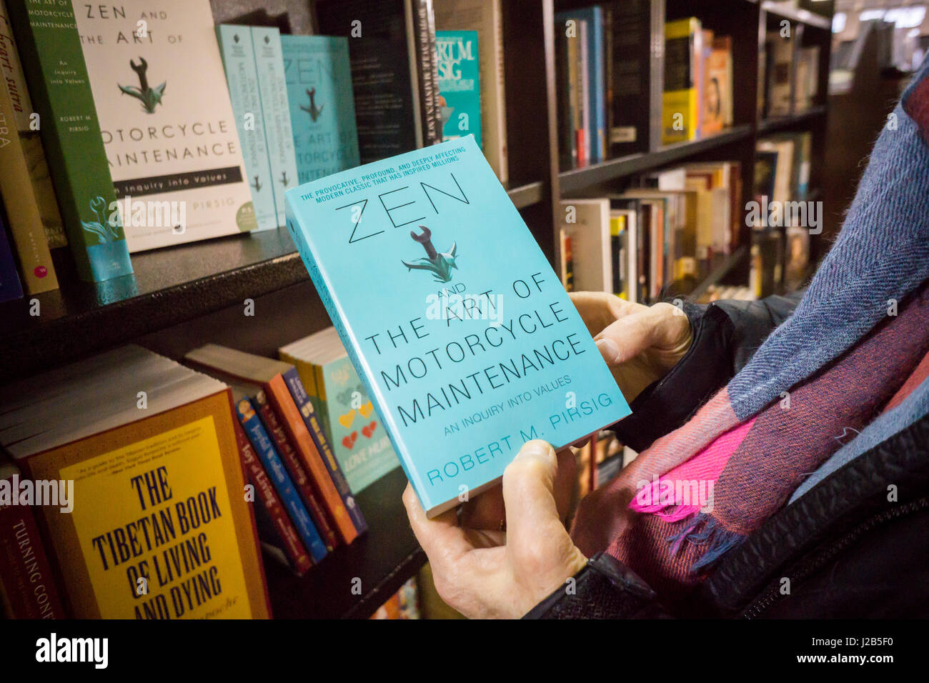 A reader holds a copy  of 'Zen and the Art of Motorcycle Maintenance: An Inquiry into Values' by Robert - Stock Image