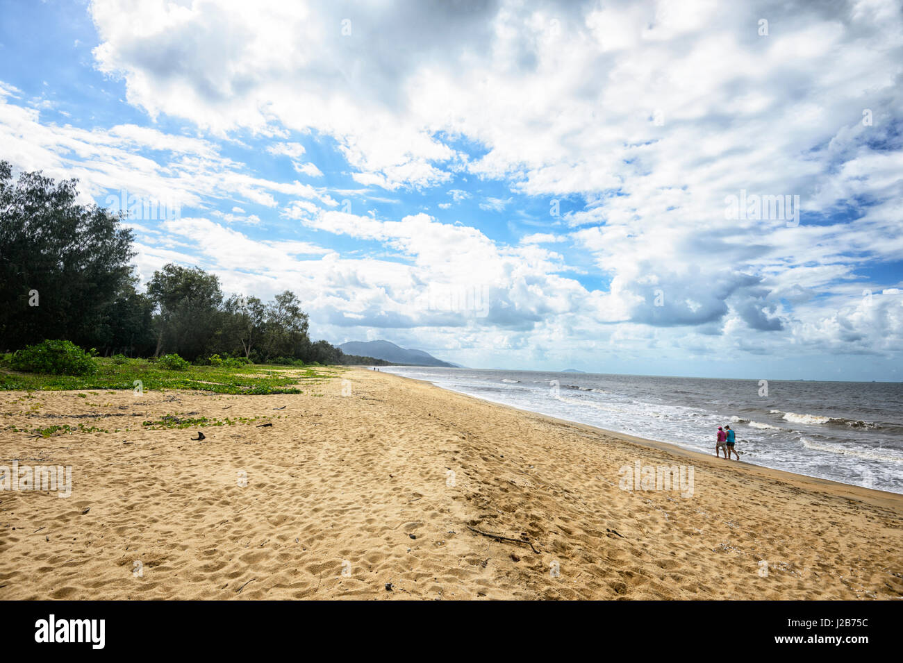 Two persons walking on the beach at Bramston Beach, Far North Queensland, QLD, FNQ, Australia - Stock Image