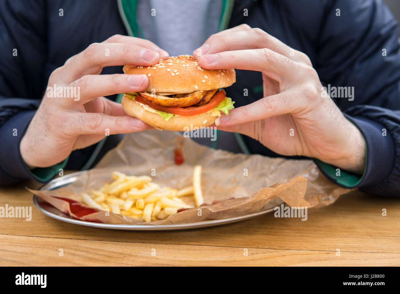 close up view of man's hands with american burger. - Stock Image
