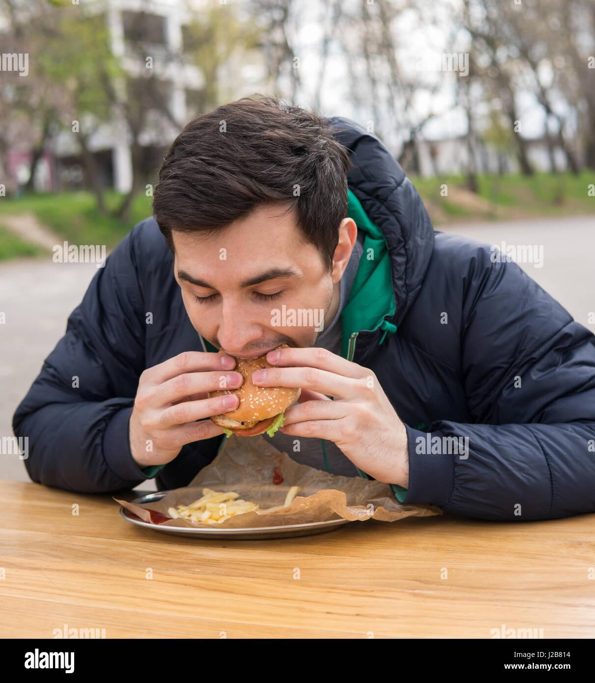man eating very tasty burger in street food cafe - Stock Image