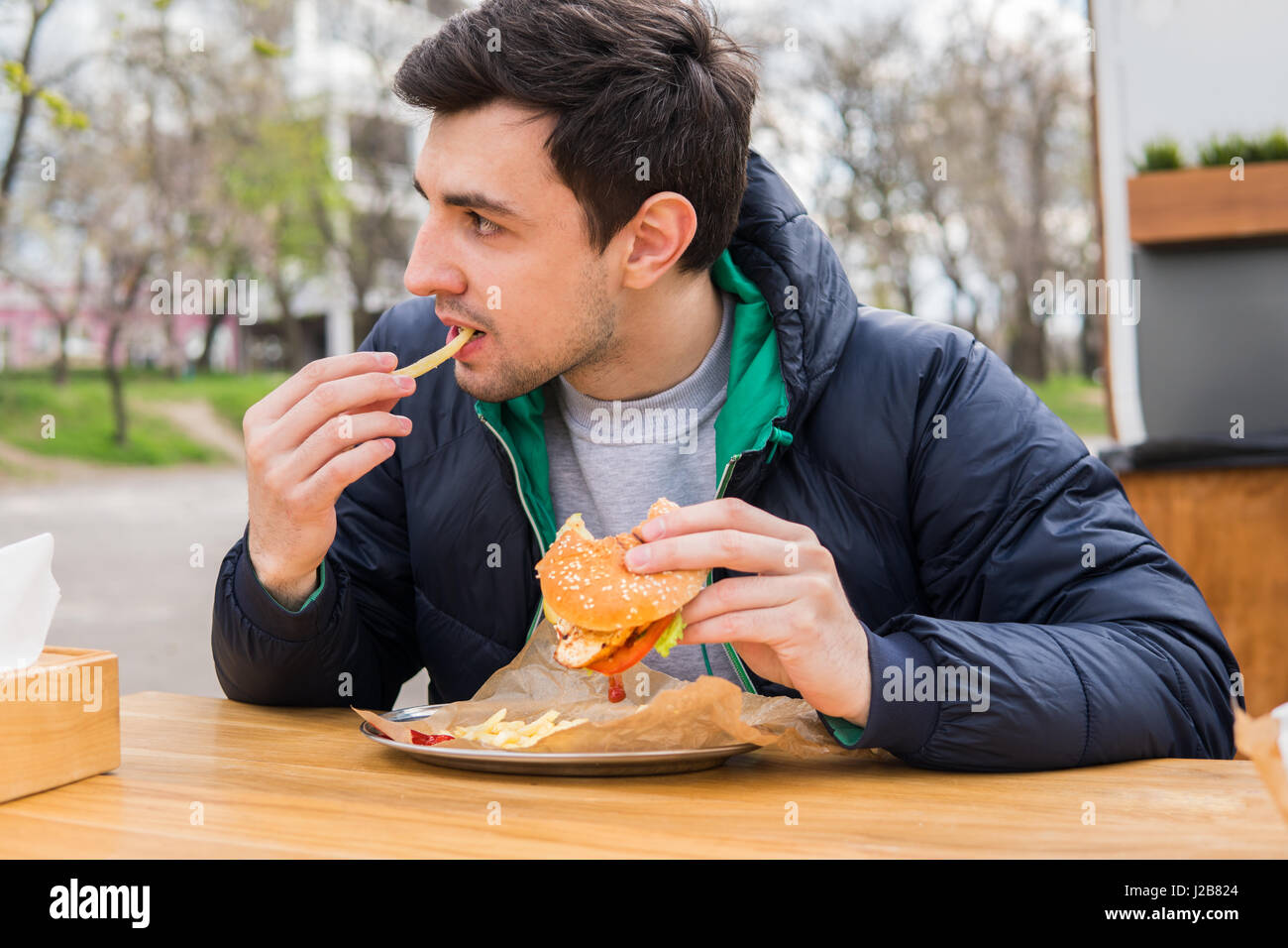 man eating fried potatoes with a burger in street food cafe - Stock Image