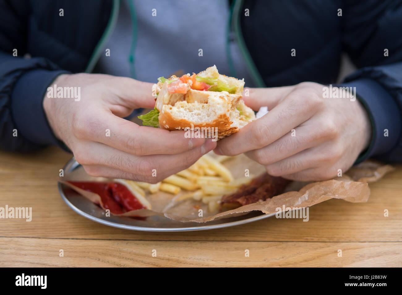 Men's hands hold a piece of bitten burger. - Stock Image