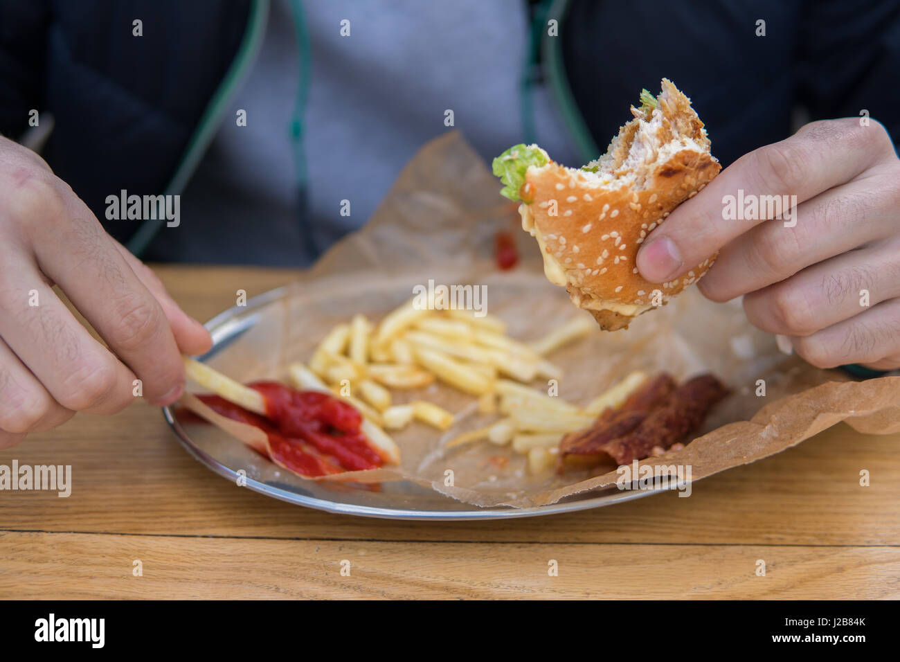 The man is eating a burger in a fast-food street diner - Stock Image
