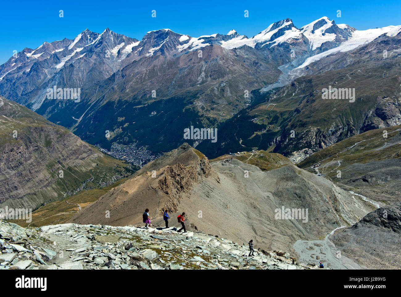 Hikers descending on the trail from the Hoernlihuette back to Zermatt, Valais, Switzerland - Stock Image