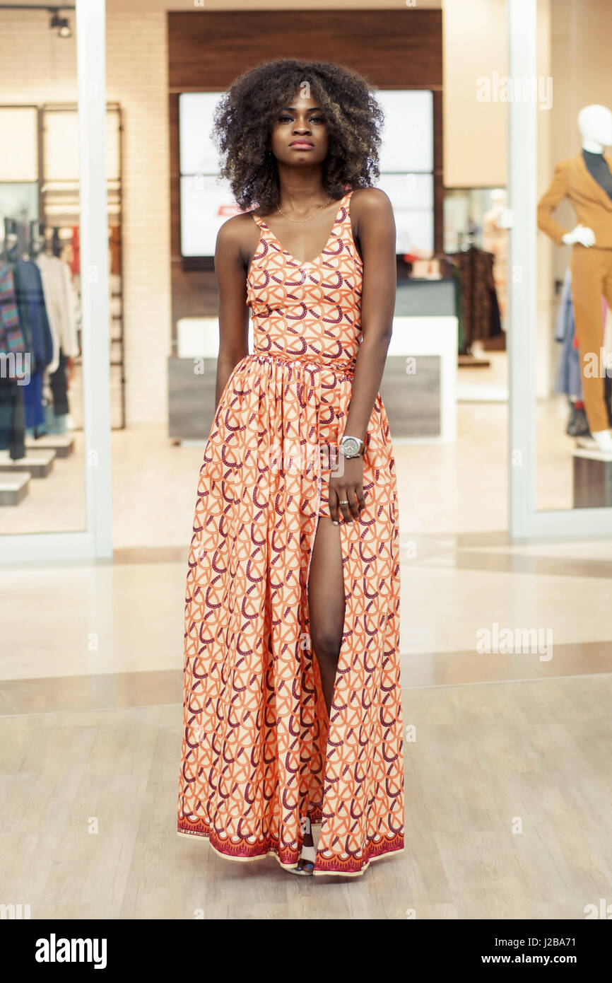 Pretty tall afro-american woman in a long dress and with curly hair  standing in a shopping mall. 4118cc11442c