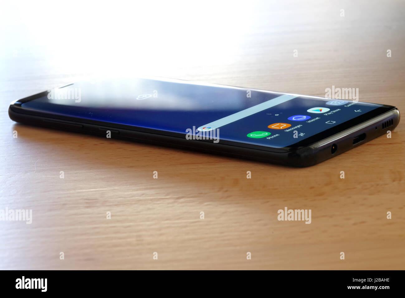Koszalin, Poland - 27 April, 2017: Black Samsung Galaxy S8 on wooden table. Samsung S8 are new generation smartphone - Stock Image