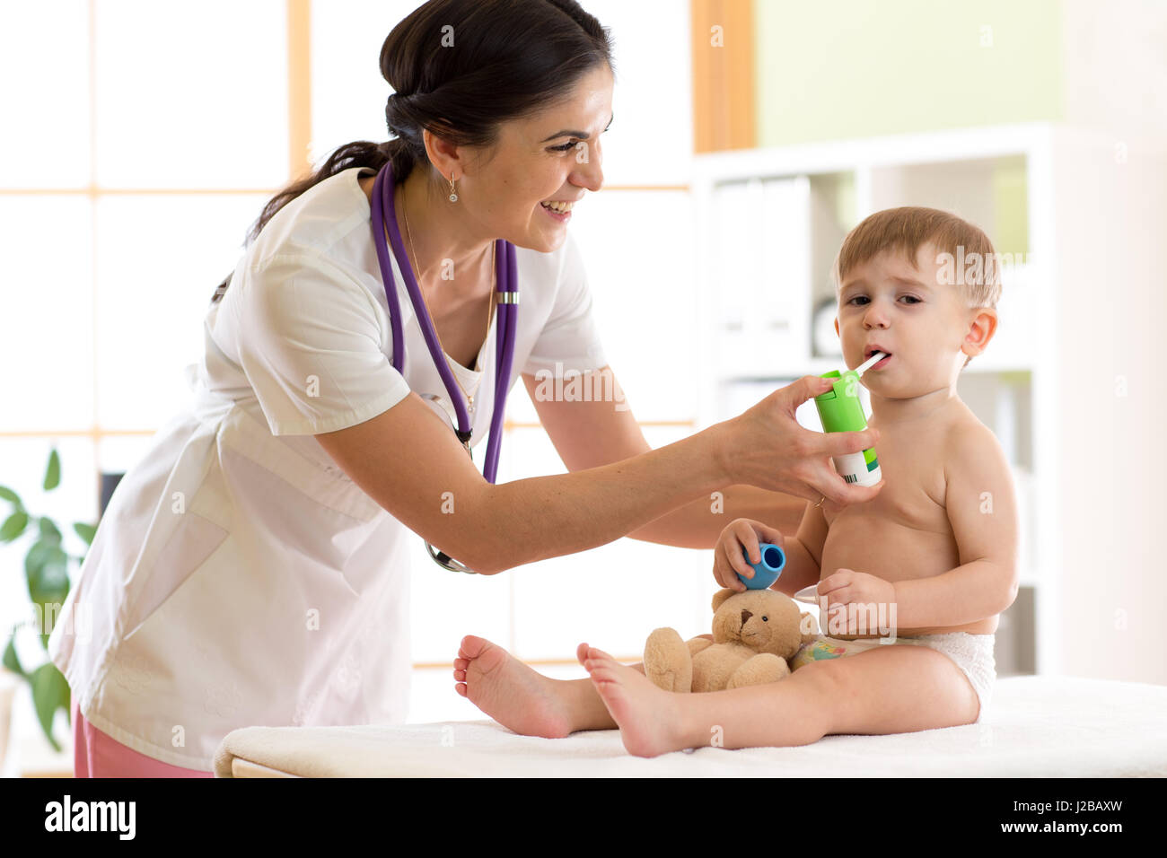Kid boy having respiratory illness helped by health professional doctor with inhaler - Stock Image
