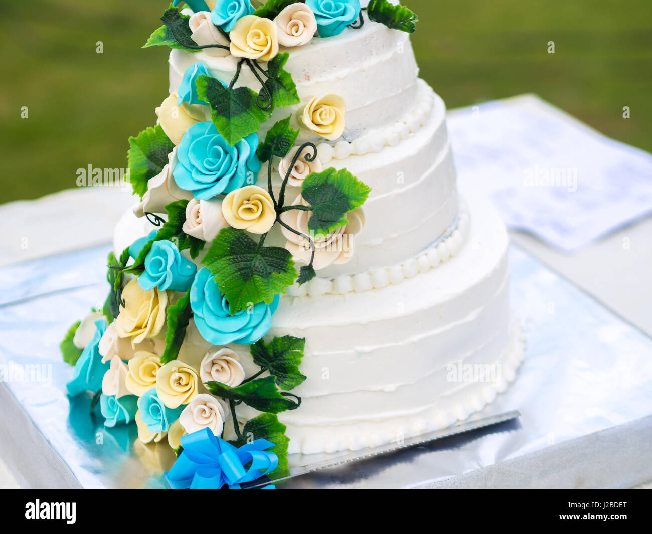 Beautiful wedding cake with blue and yellow roses - Stock Image