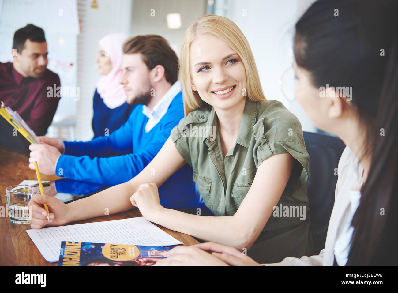 Female colleagues talking over business meeting - Stock Image