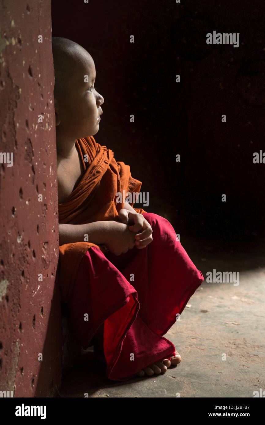 Myanmar, Yangon. A young boy monk sits in the doorway of a monastery. Stock Photo