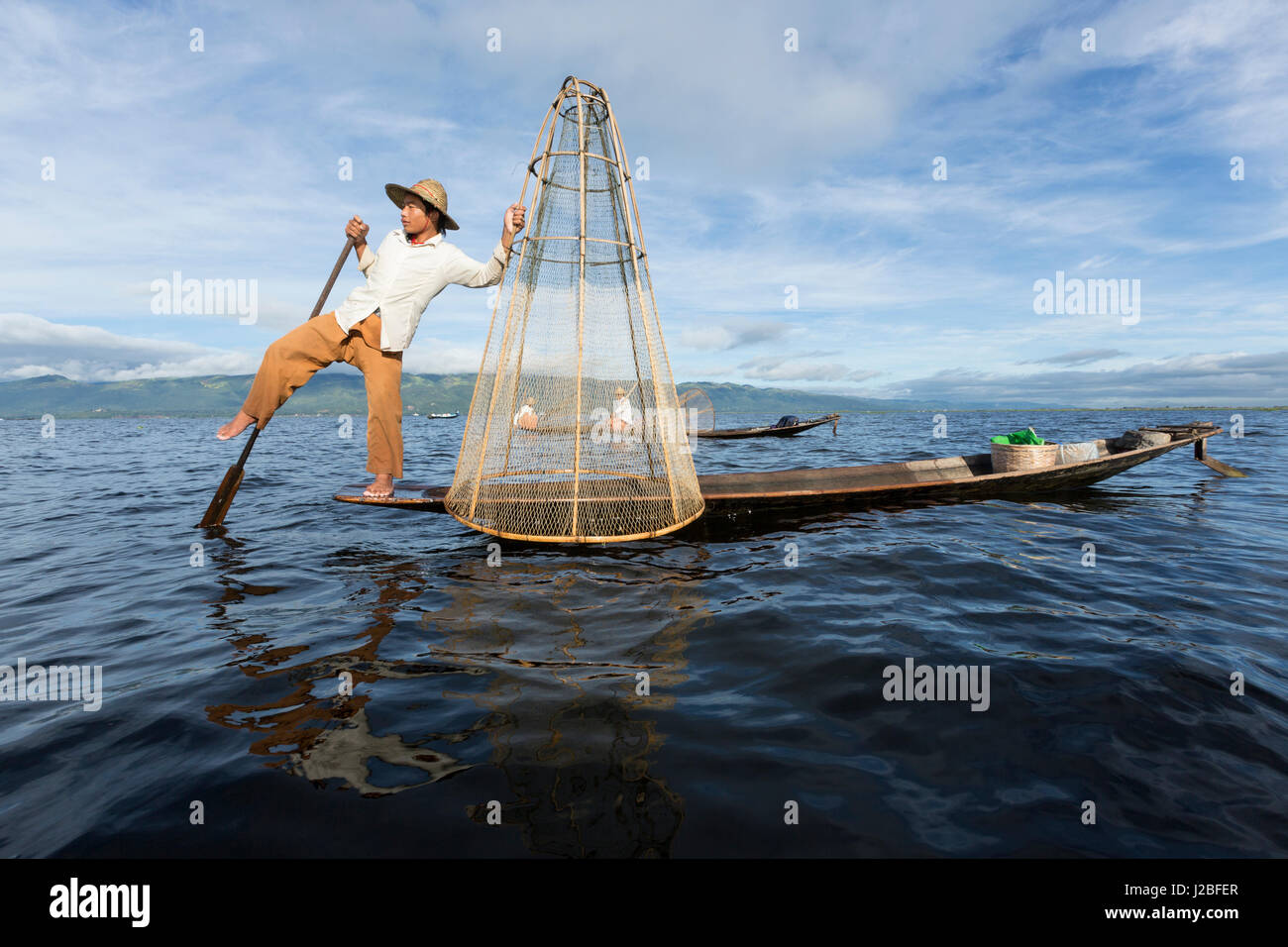 Myanmar, Inle Lake. Young fisherman demonstrates a traditional rowing technique. - Stock Image