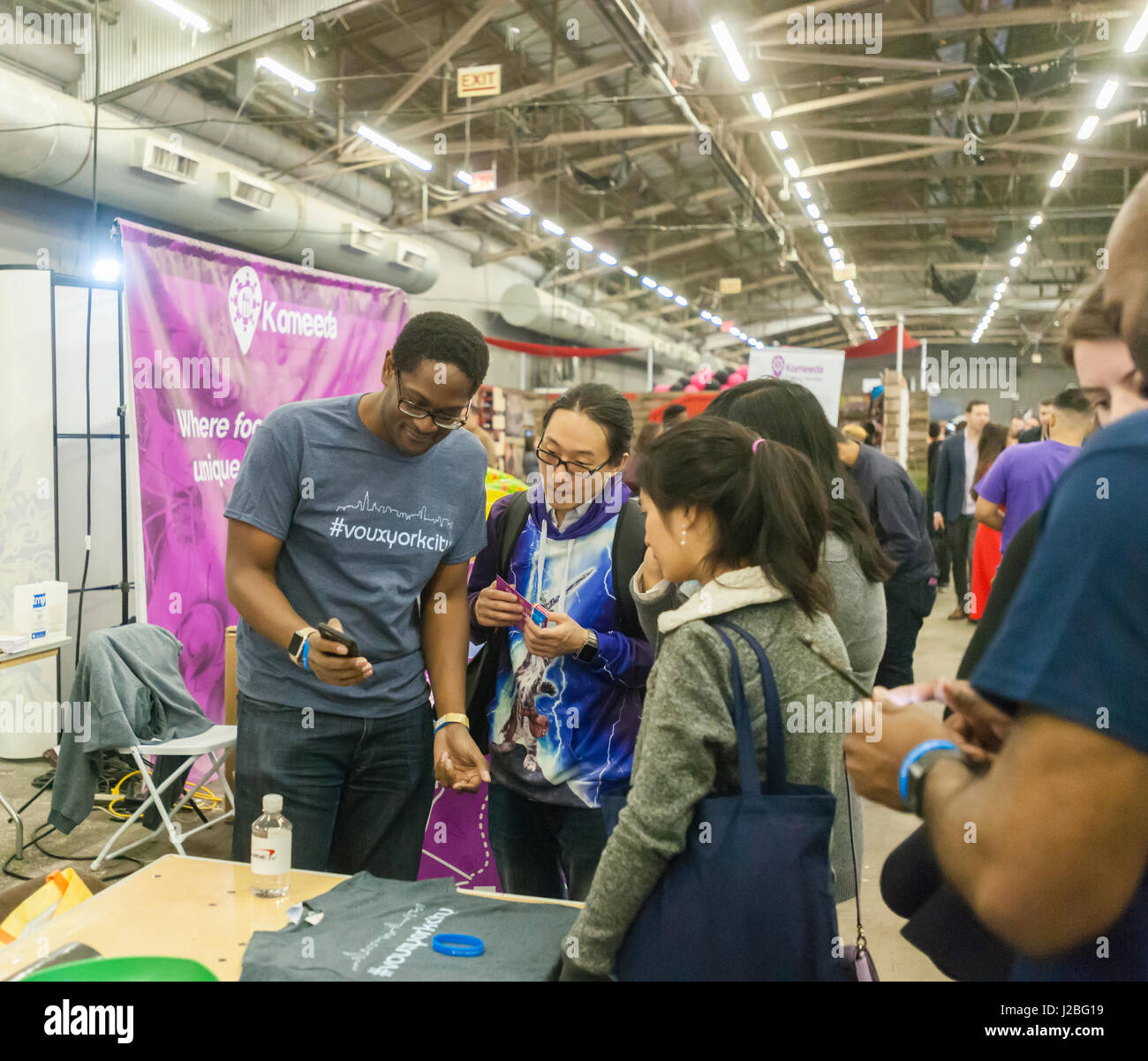 Workers from Voux speak to attendees at the TechDay New York event on Tuesday, April 18, 2017. Thousands attended - Stock Image