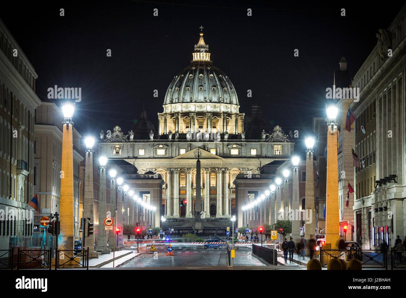View of illuminated Saint Peter Basilica, Street Via della Conciliazione and light trails of cars in Rome, Italy - Stock Image