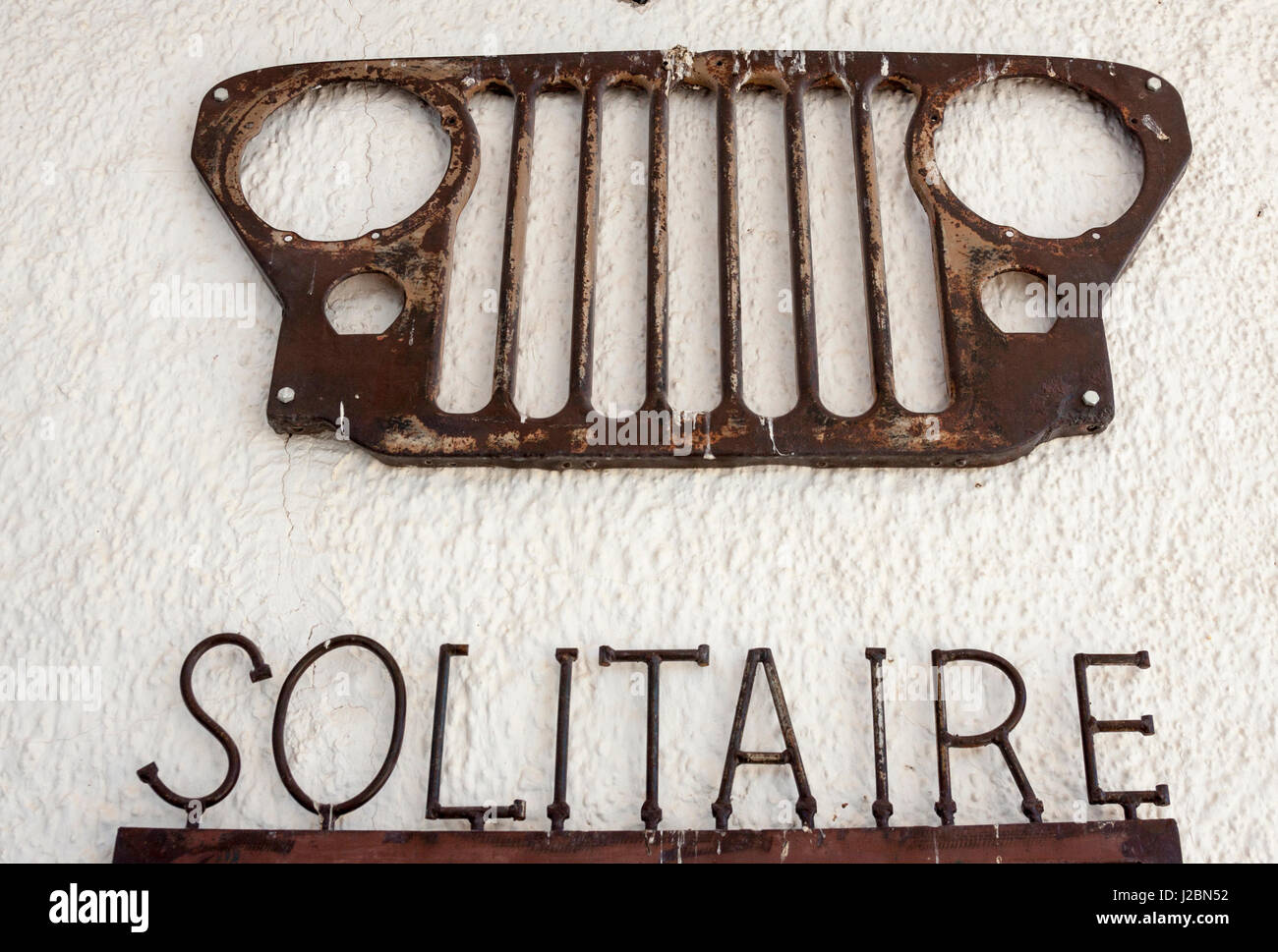 Africa, Namibia, Solitaire, Solitaire Country Lodge. Metal sign and vehicle grille on wall. Credit as: Wendy Kaveney - Stock Image