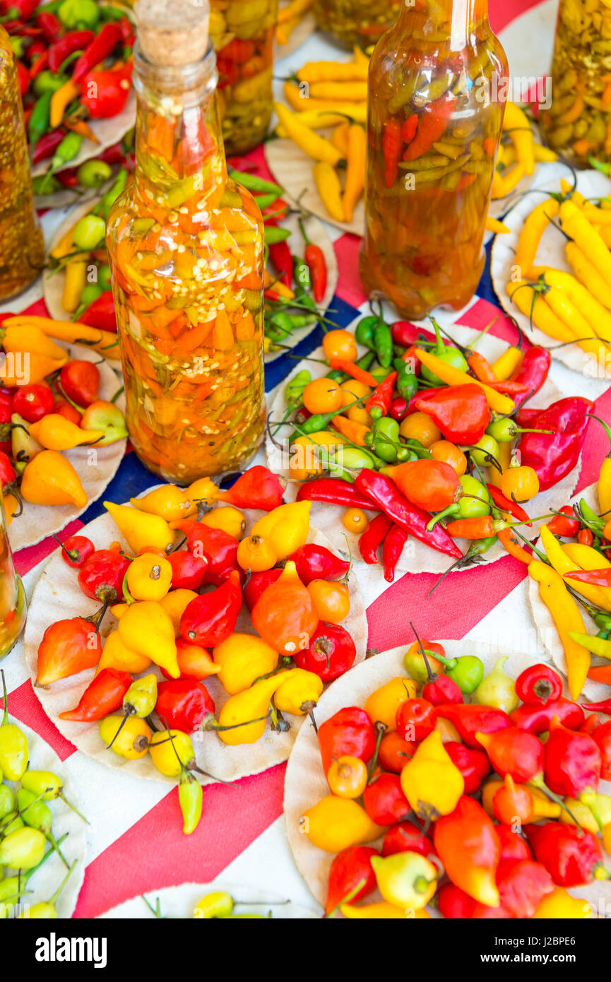 Colorful display of hot peppers in yellow, red, and orange strengths at a farmers market in Rio de Janeiro, Brazil - Stock Image