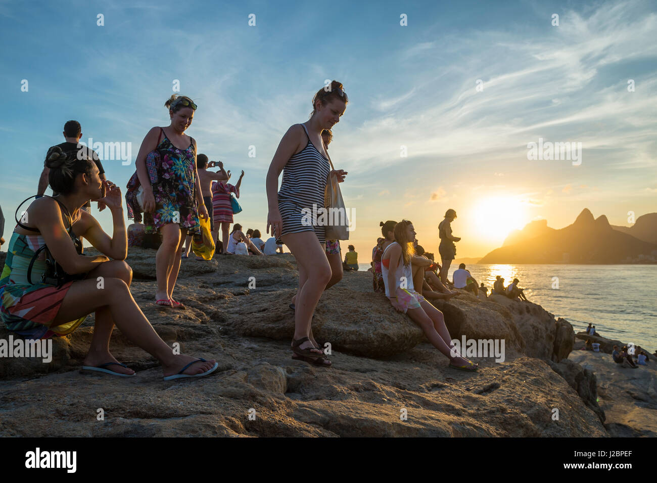 RIO DE JANEIRO - FEBRUARY 20, 2017: Crowds of visitors flock to the rocks at Arpoador to watch sunset, an increasingly - Stock Image
