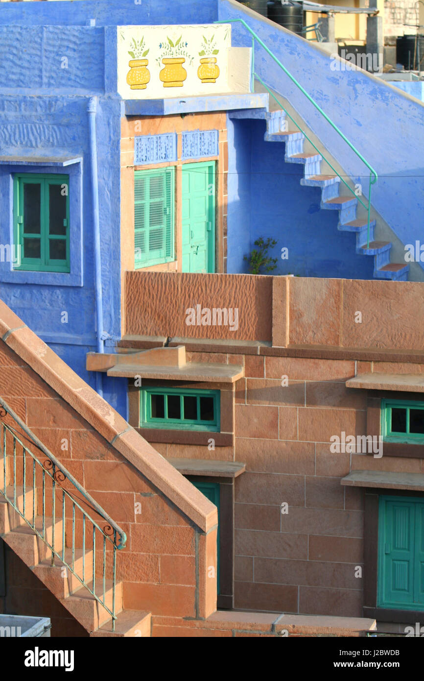 Blue City, Jodhpur, India. Blue apartment with a teal, green door, and painted flower pots, and a brick stairwell Stock Photo